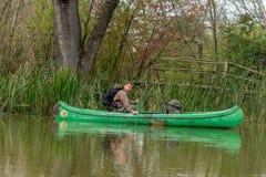 Uomo in vecchia canoa sul fiume - paesaggio immagine stock