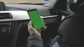 Uomo VERDE dello SCHERMO che tiene il suo smartphone in un'automobile stock footage