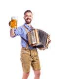 Uomo in vestiti bavaresi che tengono birra, giocante fisarmonica Oktober fotografie stock