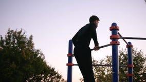 Uomo in vestiti di sport che fanno gli esercizi sulla barra orizzontale fuori nel campo sportivo nel parco Giovane che fa tirata archivi video