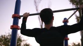 Uomo in vestiti neri di sport che fanno gli esercizi sulla barra orizzontale fuori nel campo sportivo nel parco Fondo verde degli video d archivio