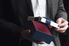 Uomo in vestito che apre un regalo con il nastro blu Fotografia Stock