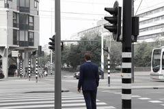 Uomo in vestito che attraversa la strada immagine stock