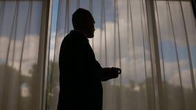 Uomo in vestito che cammina davanti alla grande finestra video d archivio