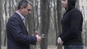Uomo in vestito che compra una pistola per soldi Dando i bancnotes al commerciante Trattare illegale dell'arma archivi video