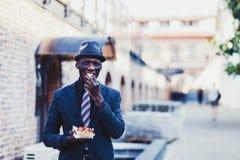 Uomo in vestito che mangia alimenti a rapida preparazione fotografia stock