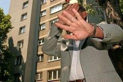 Uomo in vestito che nasconde il suo fronte Immagini Stock