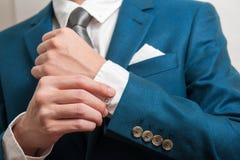 Uomo in vestito che regola le maniche Immagine Stock