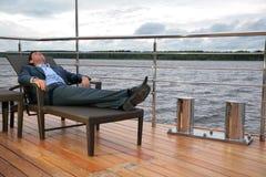 Uomo in vestito, che riposa nel salotto del chaise sul molo immagine stock libera da diritti