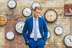Uomo in vestito che sta parete vicina con gli orologi fotografia stock libera da diritti