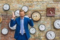 Uomo in vestito che sta parete vicina con gli orologi Fotografie Stock