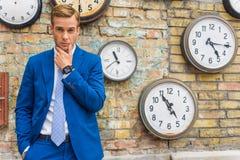 Uomo in vestito che sta parete vicina con gli orologi Immagini Stock