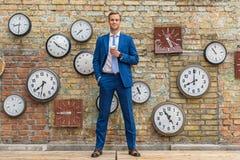 Uomo in vestito che sta parete vicina con gli orologi Fotografia Stock
