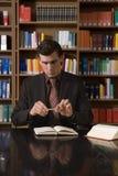 Uomo in vestito che tiene lo scrittorio di Pen Over Book At Library Fotografia Stock Libera da Diritti