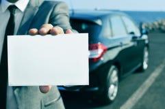 Uomo in vestito che tiene un'insegna in bianco con un'automobile nel backgrou Fotografie Stock Libere da Diritti