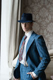 Uomo in vestito e cappello che sta alla finestra che mette la sua mano in sua tasca Fotografia Stock Libera da Diritti