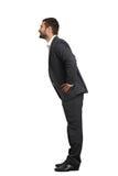 Uomo in vestito nero che pende in avanti fotografia stock libera da diritti