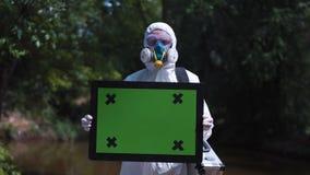 Uomo in vestito protettivo che tiene schermo verde video d archivio