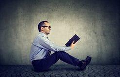 Uomo in vetri che legge un libro che si siede su un pavimento Immagine Stock Libera da Diritti