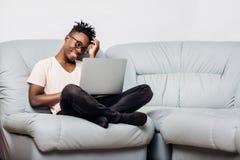 Uomo in vetri che si siedono con il computer portatile sul sofà Fotografia Stock Libera da Diritti