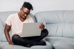 Uomo in vetri che si siedono con il computer portatile sul sofà Immagine Stock Libera da Diritti