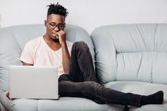 Uomo in vetri che si siedono con il computer portatile sul sofà Fotografia Stock