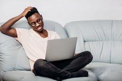 Uomo in vetri che si siedono con il computer portatile sul sofà Fotografie Stock