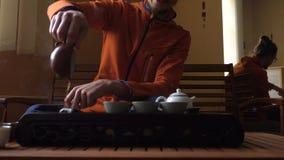 Uomo in vetri che versano il tè del puer in teiera alla cerimonia di tè del cinese tradizionale Insieme di attrezzatura per tè be stock footage