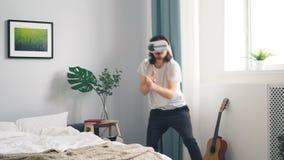 Uomo in vetri dell'AR che giocano la fucilazione del video gioco di guerra che gesturing nella camera da letto a casa stock footage