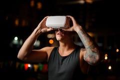 Uomo in vetri di realtà virtuale contro lo sfondo di una città di notte Fotografie Stock Libere da Diritti