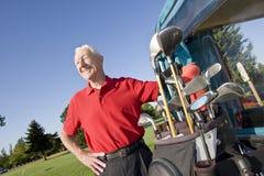 Uomo vicino a sorridere del carrello di golf Fotografie Stock Libere da Diritti