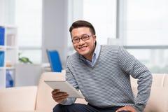 Uomo vietnamita con una compressa digitale Immagine Stock