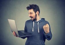 Uomo vittorioso contento con il computer portatile Fotografia Stock Libera da Diritti