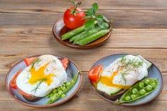Uova affogate con i pomodori e pipi su fondo di legno fotografia stock