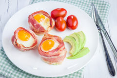 Uova al forno con l'avocado in tazze del bacon Fotografie Stock