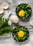 Uova al forno con spinaci su un fondo di legno leggero Fotografia Stock