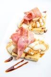 Uova Benedict con il prosciutto su pane tostato con formaggio Immagini Stock