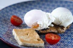 Uova Benedict con la bistecca, i pomodori ed il pane tostato della carne trovantesi su un piatto blu fotografia stock