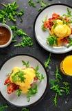 Uova Benedict sul muffin inglese con bacon croccante, l'insalata di razzo selvaggia e la salsa olandese immagine stock