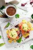 Uova Benedict sul muffin inglese con il salmone affumicato, il preparato dell'insalata della lattuga e la salsa olandese sul bord fotografia stock libera da diritti