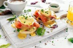 Uova Benedict sul muffin inglese con il salmone affumicato, il preparato dell'insalata della lattuga e la salsa olandese sul bord fotografia stock