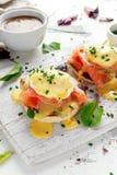 Uova Benedict sul muffin inglese con il salmone affumicato, il preparato dell'insalata della lattuga e la salsa olandese sul bord fotografie stock libere da diritti