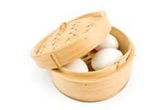 Uova bianche in cestino di bambù sotto il coperchio immagini stock