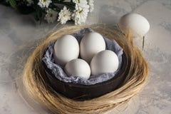 Uova bianche in ciotola di legno su fondo bianco, focuse selettivo Immagini Stock