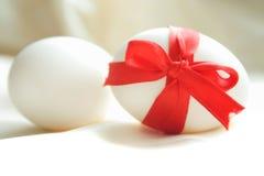 Uova bianche con l'arco rosso sopra priorità bassa bianca Fotografie Stock