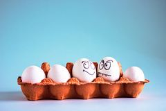Uova bianche del pollo divertente con i fronti in una cellula dell'uovo fotografie stock libere da diritti