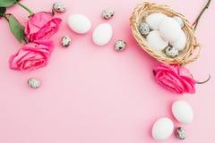 Uova bianche di Pasqua ed uova di quaglia in fiori delle rose e della scatola sul fondo di rosa pastello, vista superiore Fotografia Stock