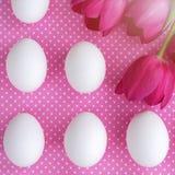 Uova bianche e fiori rosa sul tessuto del pois Immagini Stock Libere da Diritti