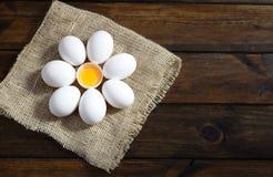Uova bianche su un sacco in un cerchio con l'uovo aperto nel mezzo su legno Fotografie Stock Libere da Diritti