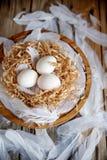 Uova bianche in un nido decorativo su un piatto di legno Umore di Pasqua di concetto di Pasqua fotografia stock